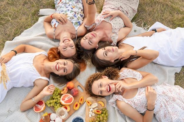 Вид сверху. компания красивых подружек повеселится и устроит пикник на природе.