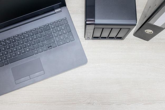 Вид сверху для офисного рабочего места с ноутбуком и сервером резервного копирования nas на деревянном фоне.