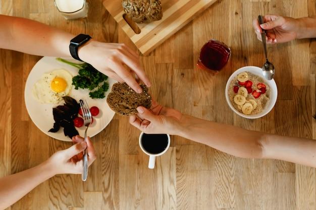 위에서 손으로 보기는 한 쌍을 위한 빵 아침 식사를 전달합니다.