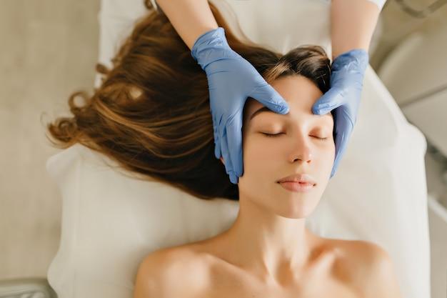 プロの美容師の頭のマッサージからリラックスできる長いブルネットの髪を持つうれしそうな女性の上からの眺め。美容、ヘルスケア、若返りの時間