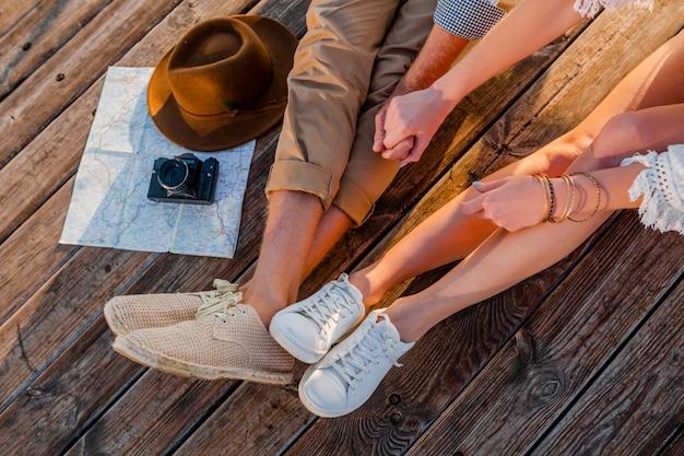Вид сверху ноги пары, путешествующей летом, одетой в кроссовки