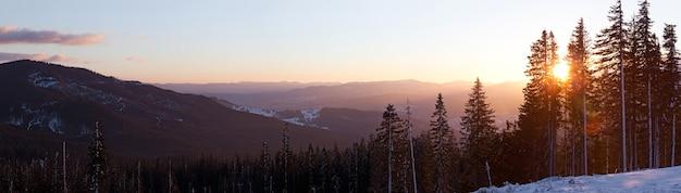 Вид сверху завораживающе живописный пейзаж горных хребтов, покрытых густыми и заснеженными еловыми лесами на фоне заходящего солнца ясным зимним вечером.