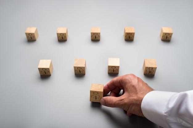 회색 배경에 사람 아이콘이 있는 나무 큐브를 배열하는 사업가의 위에서 봅니다. 인적 자원의 개념입니다.