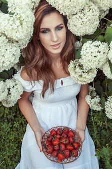 たくさんのイチゴを持って、白い薄手のドレスを着た美しい女性の上からの眺め。屋外の春または夏の写真
