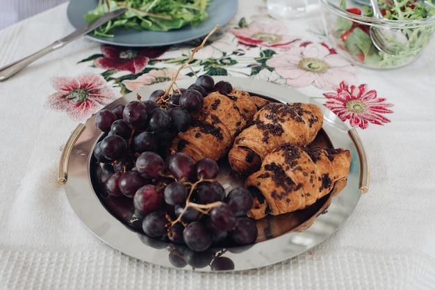 Вид сверху на вкусные шоколадные круассаны и виноград