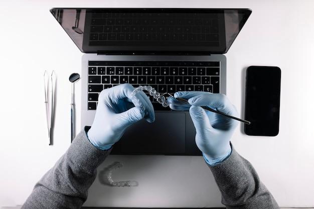 歯科用アライナーで作業している医師の手の上からの眺め