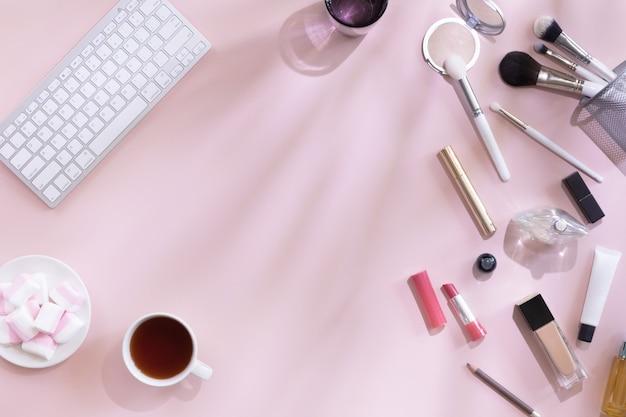 Взгляд сверху места для работы блогера моды с компьютером, чашкой кофе или чая, женским аксессуаром, косметическими продуктами на розовой предпосылке с тенью и трудным светом. плоский дизайн, концепция красоты