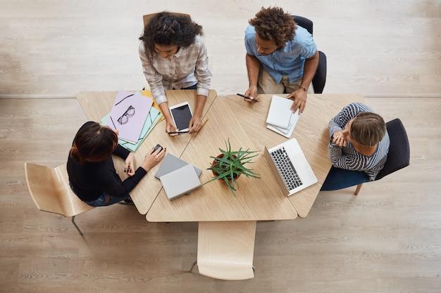 Вид сверху группы молодых профессиональных предпринимателей, сидящих за столом в коворкинг-пространстве, обсуждающих прибыль последнего командного проекта, используя ноутбук, цифровой планшет и смартфон.