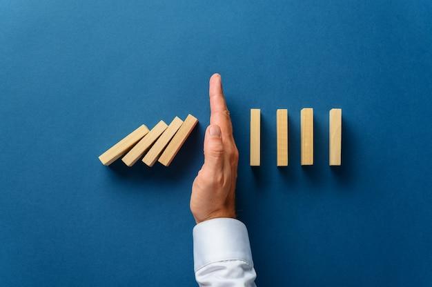 ビジネス危機管理の概念的なイメージで崩壊するドミノを妨害する男性の手の上からの眺め。