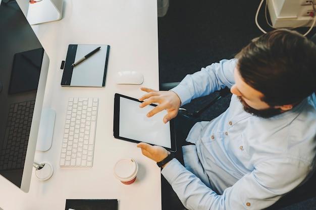 컴퓨터와 책상에 앉아 태블릿을 사용하는 남성의 위에서보기