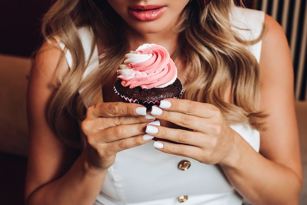 맛있는 분홍색 컵케이크를 손에 들고 있는 예쁜 여자의 위에서 볼 수 있습니다. 맛있는 달콤한 초콜릿 케이크를 보고 냄새를 즐기는 젊은 여성. 과자와 디저트의 개념입니다.
