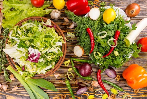 나무 테이블에 로즈마리, 양상추, 부추, 양파, 고추, 레몬 및 기타 맛있는 재료의 위에서보기