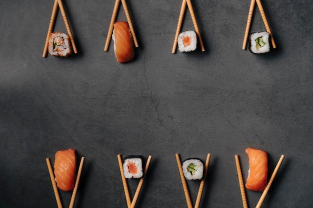 Вид сверху на некоторые японские суши-роллы и несколько кусочков лосося с рисом, принимающих очень оригинальную форму с помощью палочек для еды. вид сверху..