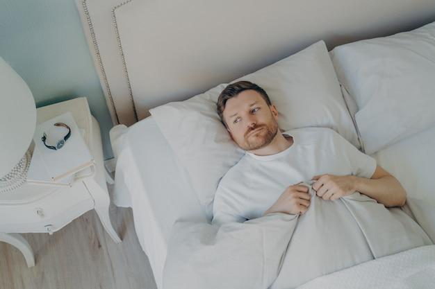 스트레스를 받고 있는 젊은 백인 남성이 눈을 뜨고 잠을 잘 수 없는 상태에서 침대에 누워 있는 모습, 불면증 문제로 인해 불행하고 피곤함을 느끼는 남성. 취침 및 휴식 문제 개념