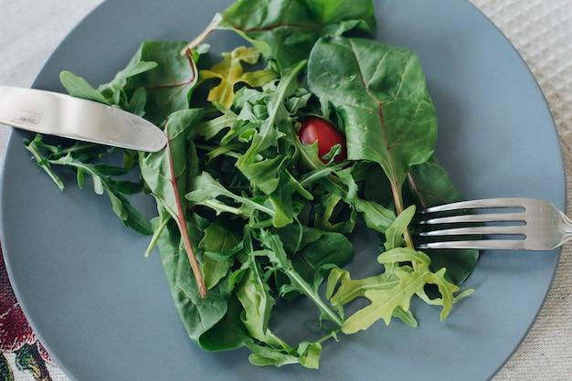 Вид сверху помидоров и зелени, лежащих на тарелке