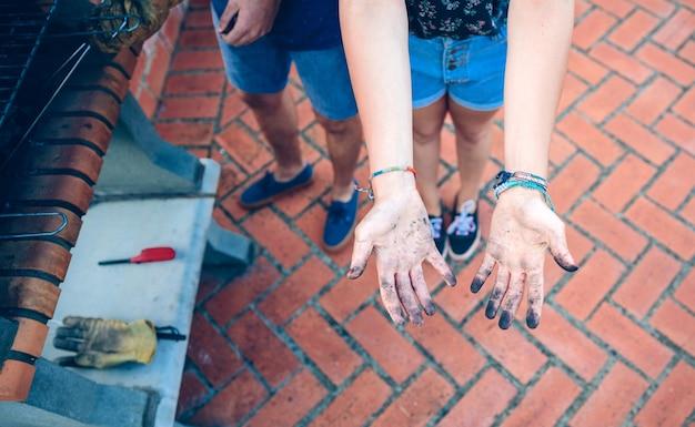 Вид сверху неузнаваемой молодой женщины, показывающей руки, грязные от угля для барбекю