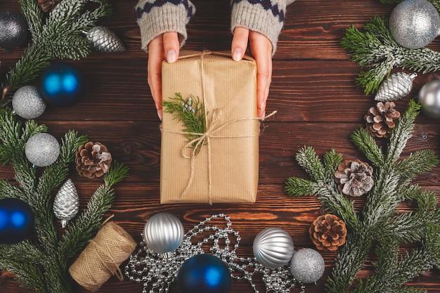 Вид сверху на женщину в свитере с украшенным подарком