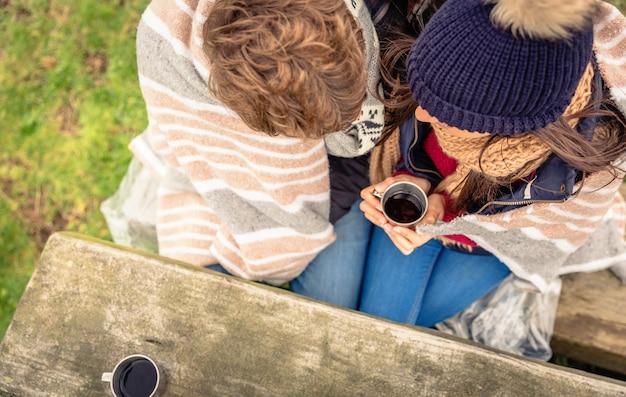 추운 날 야외에서 뜨거운 음료를 마시는 줄무늬 담요 아래 젊은 부부의 위에서 보기