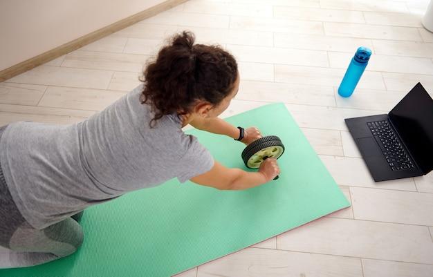 운동 튜토리얼을보고 집에서 체조 롤러를 사용하여 복근 운동을하는 스포티 한 여자 위에서보기