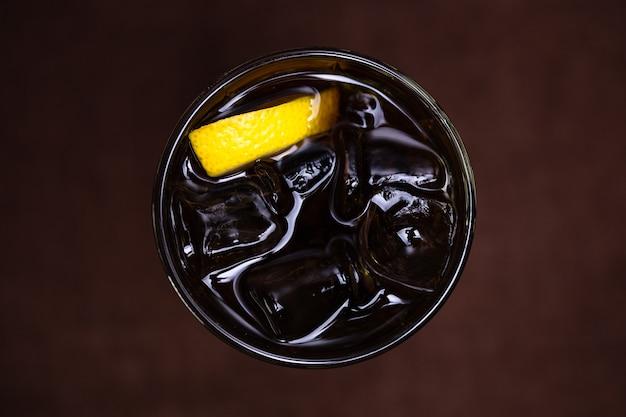 Вид сверху на алкогольный коктейль со льдом и цитрусовыми.