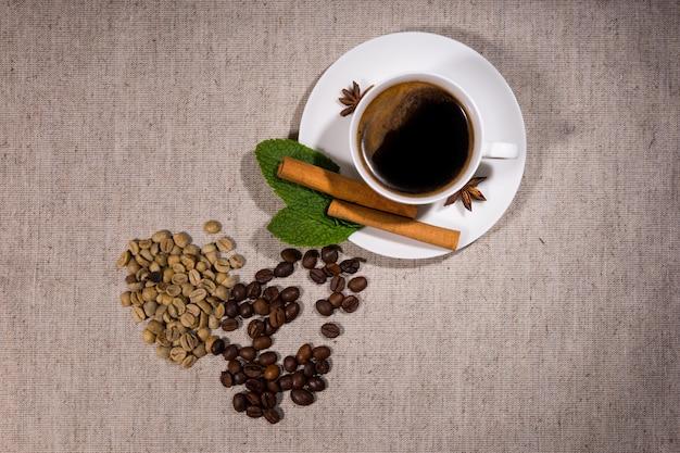 灰色のテーブルクロスの上にコーヒーとソーサーでいっぱいの熱いティーカップの横にあるさまざまな種類のjavabeansとハーブを上から見る
