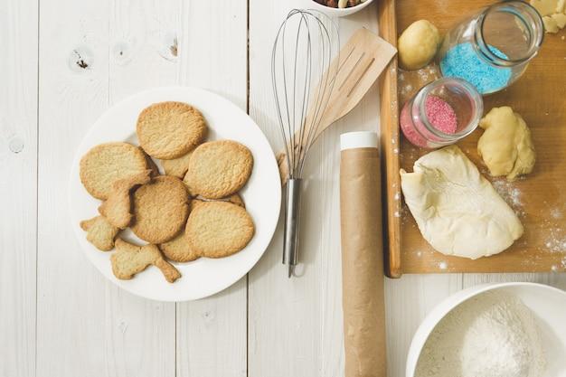 皿の上の調理済みクッキーとテーブルの上の台所用品を上から見る