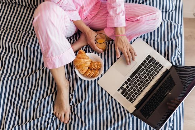 朝食を持っているラップトップとベッドに座っているピンクのパジャマの若い女性の手で上からの眺め