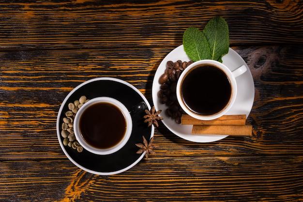 濃い色の木製テーブルの背景の上にソーサーで豆、スパイス、葉とカップでコーヒーと紅茶のサービングを上から見る