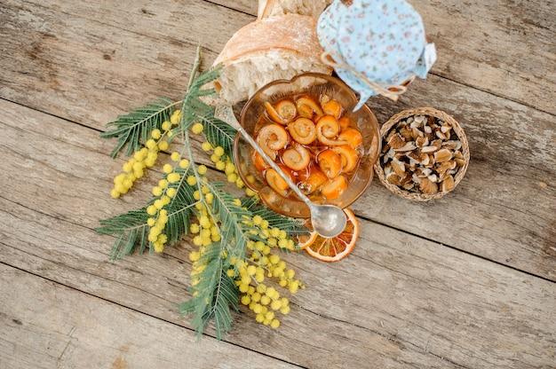 Вид сверху на засахаренную апельсиновую спиральную цедру с сахарным сиропом в стеклянной банке и тарелку возле блюдца с грецкими орехами, мимозой и хлебом на деревянном столе