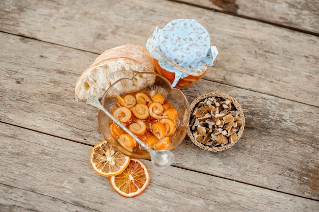 Вид сверху на засахаренную апельсиновую спиральную кожуру с сахарным сиропом в стеклянной банке и тарелку возле блюдца с грецкими орехами на деревянном столе.