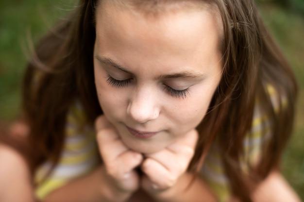 손에 머리를 대고 눈을 감고 있는 소녀의 얼굴을 위에서 본 모습