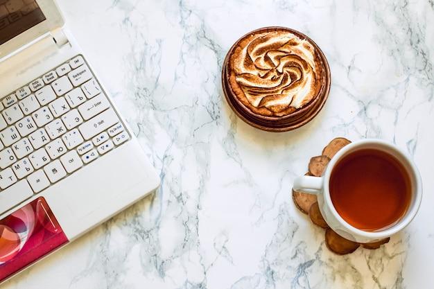 흰색 대리석 위에 있는 여성의 손을 위에서 내려다보면 흰색 노트북 근처에 차와 케이크 한 잔이 있습니다.