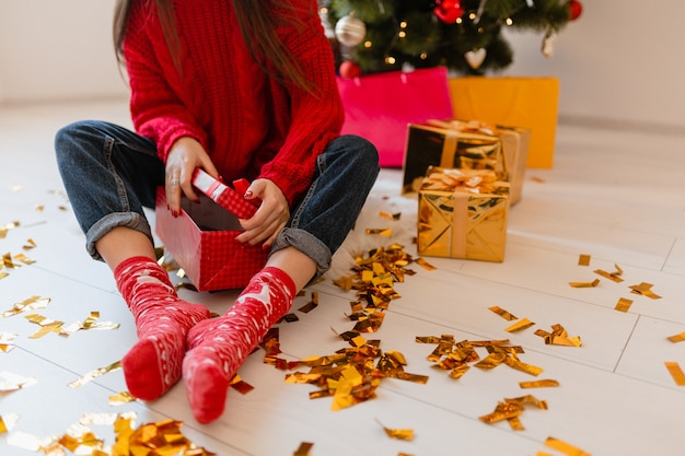 Вид сверху на женщину в красных носках, сидящую дома на рождество на золотом конфетти, распаковывающую подарки и подарочные коробки