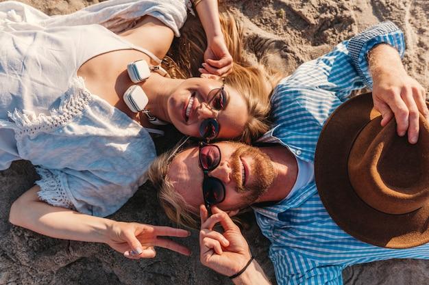 Вид сверху на молодого улыбающегося счастливого мужчины и женщины в солнцезащитных очках, лежащих на песчаном пляже