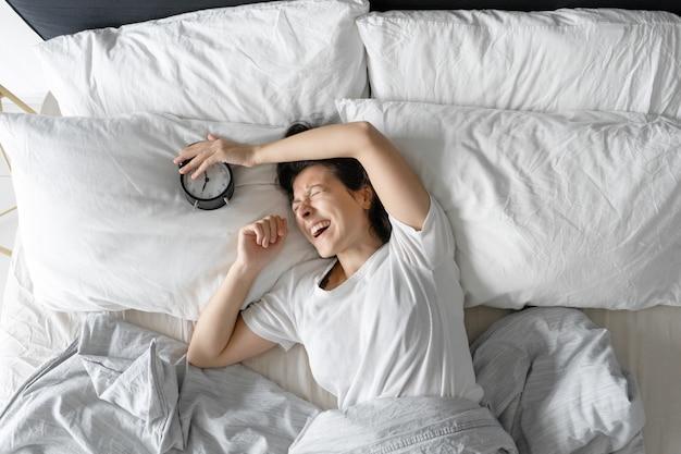 上からの眺め。女の子は目覚まし時計の隣で寝ています。睡眠を妨げる鳴っている目覚まし時計をオフにしようとしています。起きる時間。深い眠り。