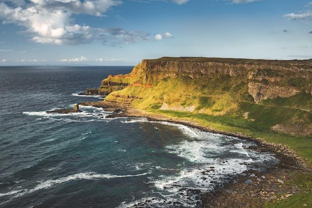 Вид сверху на береговую линию северной ирландии, поверхность воды океана рядом с покрытой травой землей
