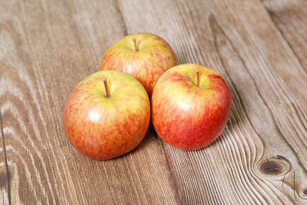 Вид сверху на три яблока за деревянным столом