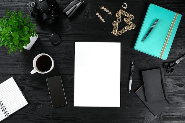 一杯のコーヒーとスマートフォン付きのコピースペースオフィステーブルノートブックで上から見る