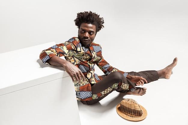 床に座っている若い大人のアフロ男をお辞儀からの眺め