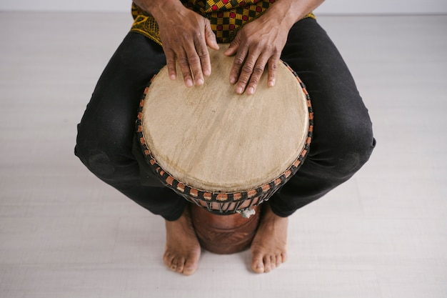 View from above of african american male musician playing traditional drums at home. online music class concept. leisure and learning musical instruments. rhythm in ethnic multicultural traditions.