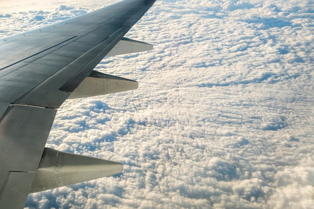 View from airplane on the aircraft white wing flying over cloudy landscape in sunny morning.