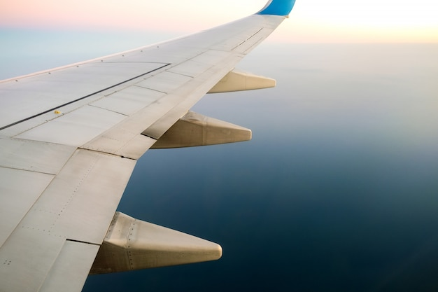 View from airplane on the aircraft white wing flying over ocean landscape in sunny morning. air travel and transportation concept.