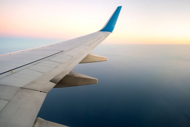View from airplane on the aircraft white wing flying over ocean landscape in sunny morning