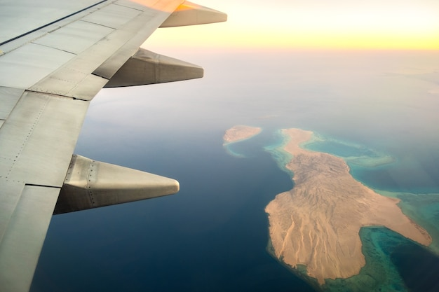 View from airplane on the aircraft white wing flying over ocean landscape in sunny morning.