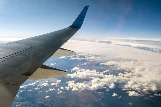 Взгляд от самолета на крыле самолета белое летая над пасмурным ландшафтом в солнечном утре. воздушные путешествия и транспорт концепция.