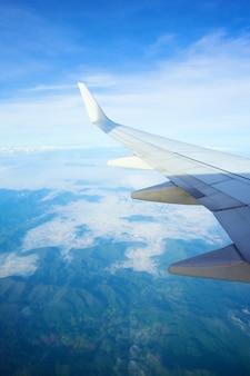 雲の上の飛行機の窓からの眺め飛行機の翼