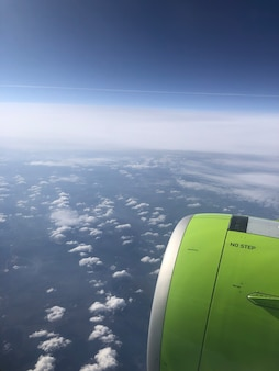 View from the airplane window of blue sky with clouds