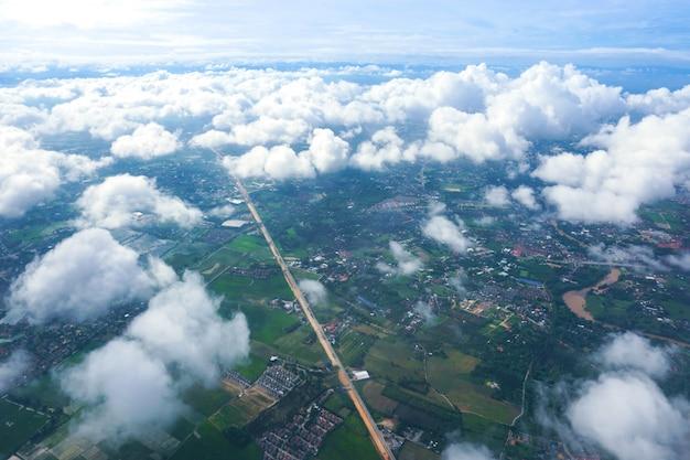 飛行機の窓の街と雲からの眺め