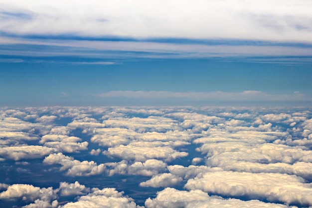View from an airplane window, flying above white clouds