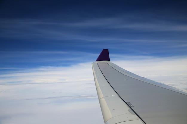 화창한 날에 흰 구름과 푸른 하늘 위에 날개에 비행기 창에서 볼 수 있습니다.